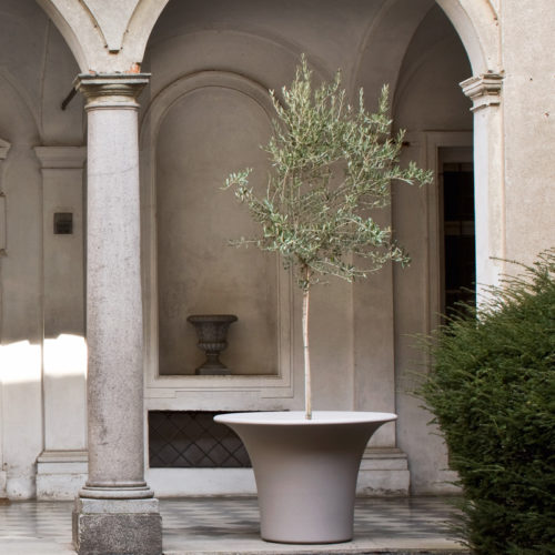 Serralunga's Cone planter in a Tuscan inspired garden setting with a tall plant and pillars