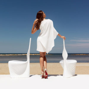A woman with two white Biophilia dining chairs by Vondom.