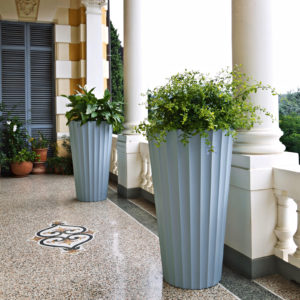 Serralunga's Eufronio planter in a shade of blue on a porch with plants