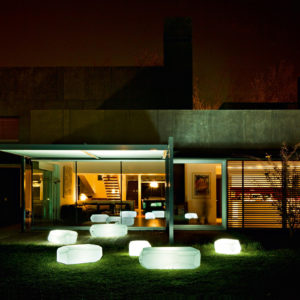 Night time shot of a few of Serralunga's light up Meteor coffee tables in a garden setting