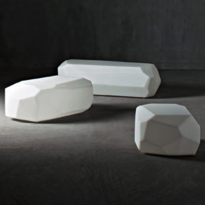 Serralunga's Meteor coffee tables in white on a lightly lit dark background