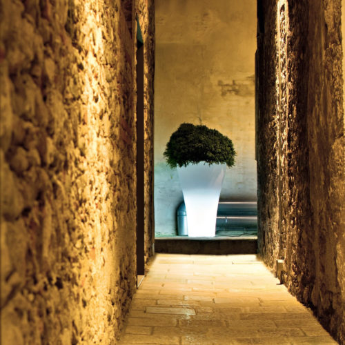 Serralunga's Ming high light up planter in a stoned corridor with a plant