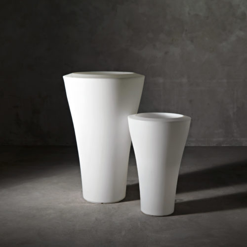Two of Serralunga's Ming high planters in white placed in a dark setting
