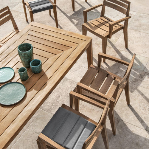 Ethimo's Ribot range dining armchair in an outside setting with dining table.