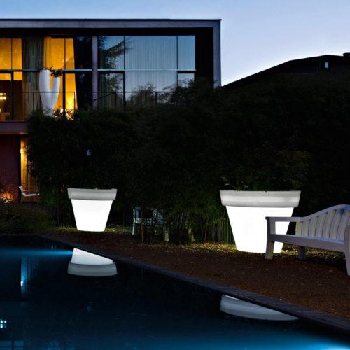 Serralunga's Vas on medium illuminated planters next to the pool in the evening light