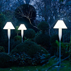 Serralunga's Bonheur floor lamps in a night time garden setting with trees