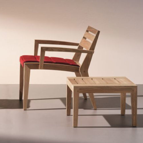 Ethimo's Ribot lounge armchair and coffee table in soft lit setting.