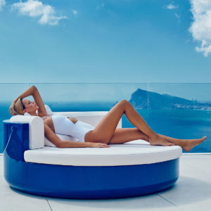 Vondom's Ulm daybed in blue, in outdoor sitting with a woman and the ocean.