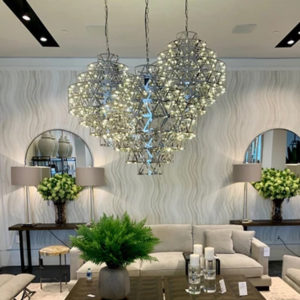 3 Clinton Chandeliers by Eichholtz displayed in a luxurious lounge setting.